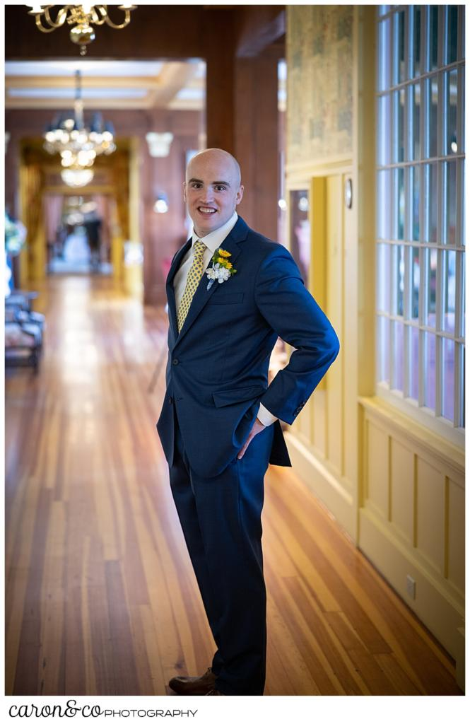 full length portrait of a groom, wearing a medium blue suite, standing in the hallway of the colony hotel, Kennebunkport maine