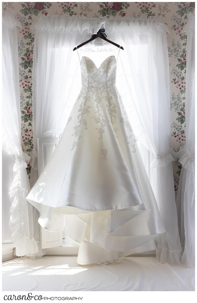 a strapless white wedding dress, with white appliqué flowers, hangs on a wooden hanger in the window of a guest room at the Colony Hotel, Kennebunkport, Maine