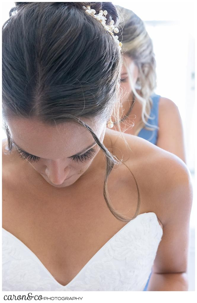 a bride having her dress zipped, has her head down, as a bridesmaid zips in the background