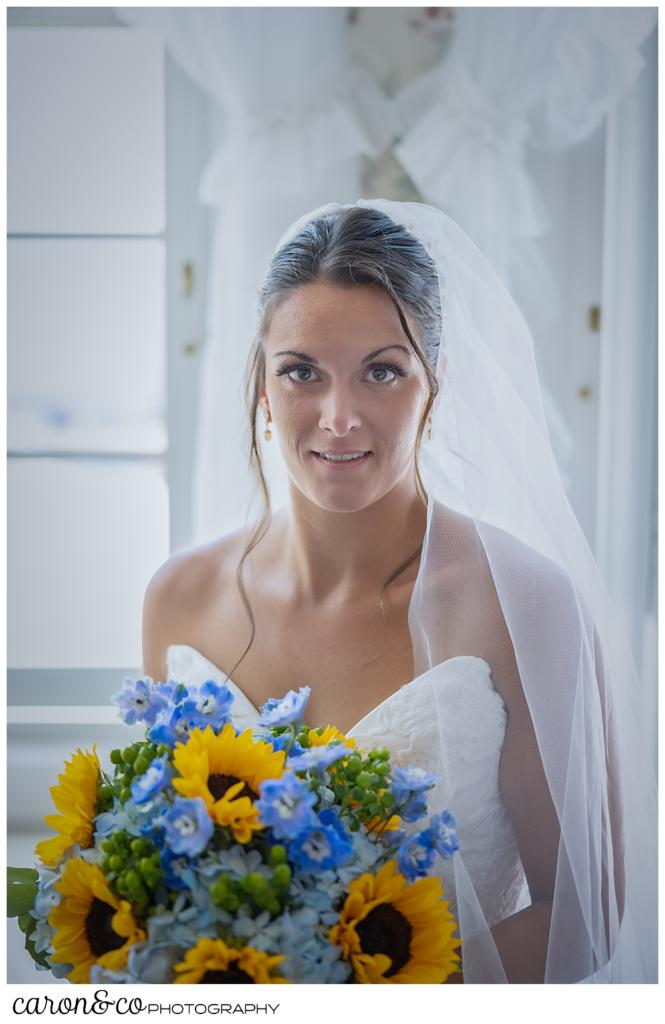 a beautiful bridal portrait of a dark haired, dark eyed bride, wearing a white sleeveless dress and veil, holding a bouquet of blue hydrangeas and yellow sun flowers, she has a slight smile