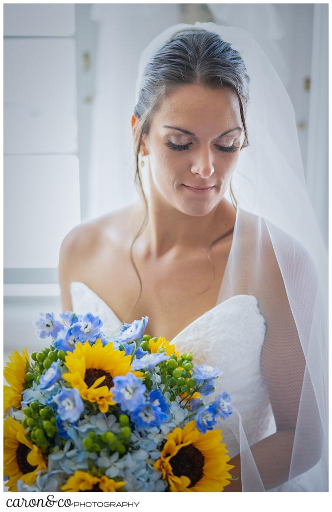 a stunning bridal portrait of a dark haired bride, her head to the right, eyes closed, wearing a white strapless gown and veil, holding a bridal bouquet of blue hydrangeas and yellow sun flowers