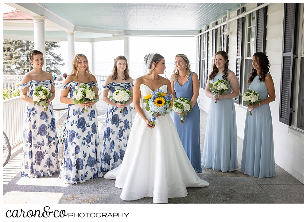a bride in white, stands in the midst of her bridesmaids, three have light blue dresses, three have blue flowered dresses
