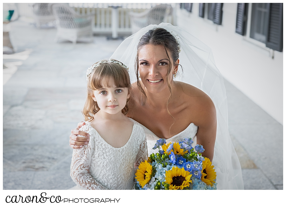 a bride kneels down next to a flower girl, they're both wearing white, the bride has a bouquet of blue hydrangeas and yellow sun flowers