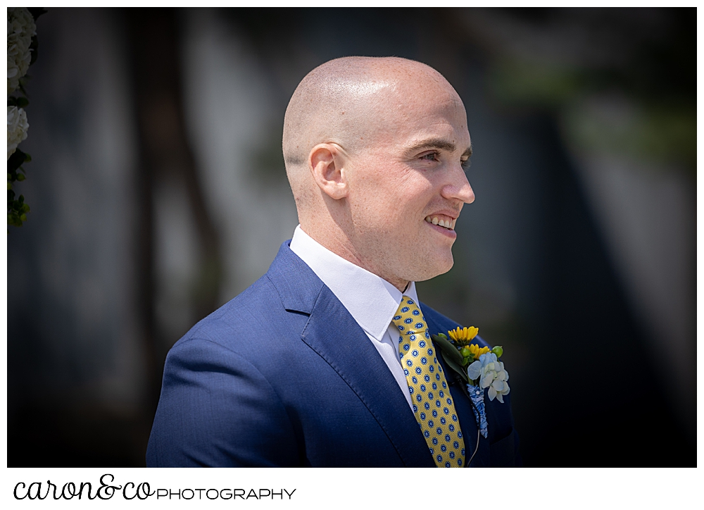 a smiling groom, wearing a blue suit, waits for his bride to come down the aisle at a Kennebunkport wedding at the Colony Hotel