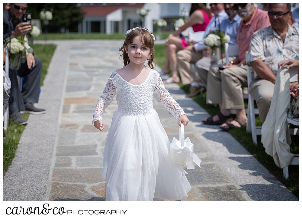 a flower girl, wearing a long white dress, drops petals on her way down the aisle at a Kennebunkport wedding at the Colony Hotel, Kennebunkport, Maine