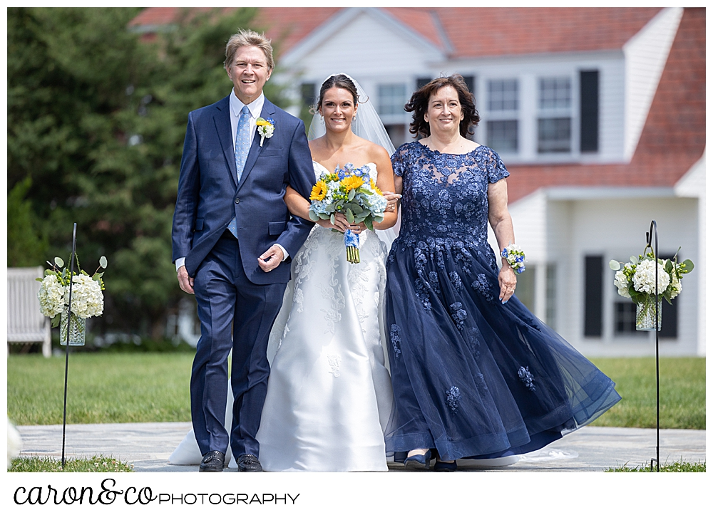 a bride, holding the arms of her mother and father, one on each side, as they walk down the aisle at a Kennebunkport wedding at the Colony Hotel, they're all smiling