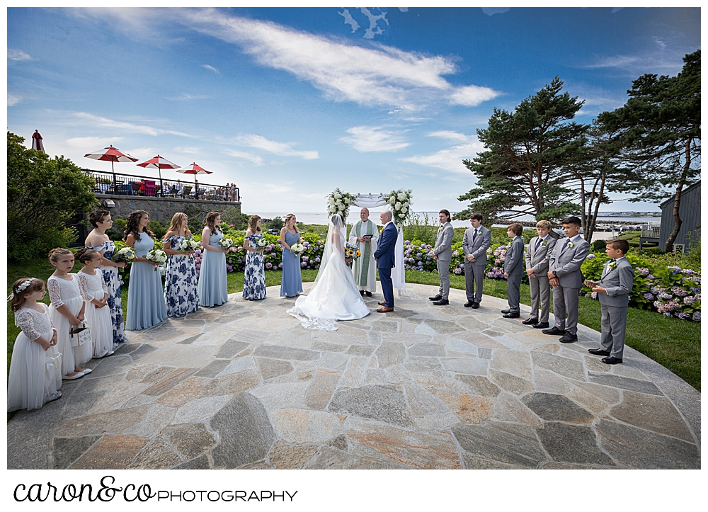 a Colony Hotel outdoor wedding ceremony, with a bride and groom and an officiant in the middle, and 6 bridesmaids and 3 flower girls on the left, and 6 groomsmen on the right