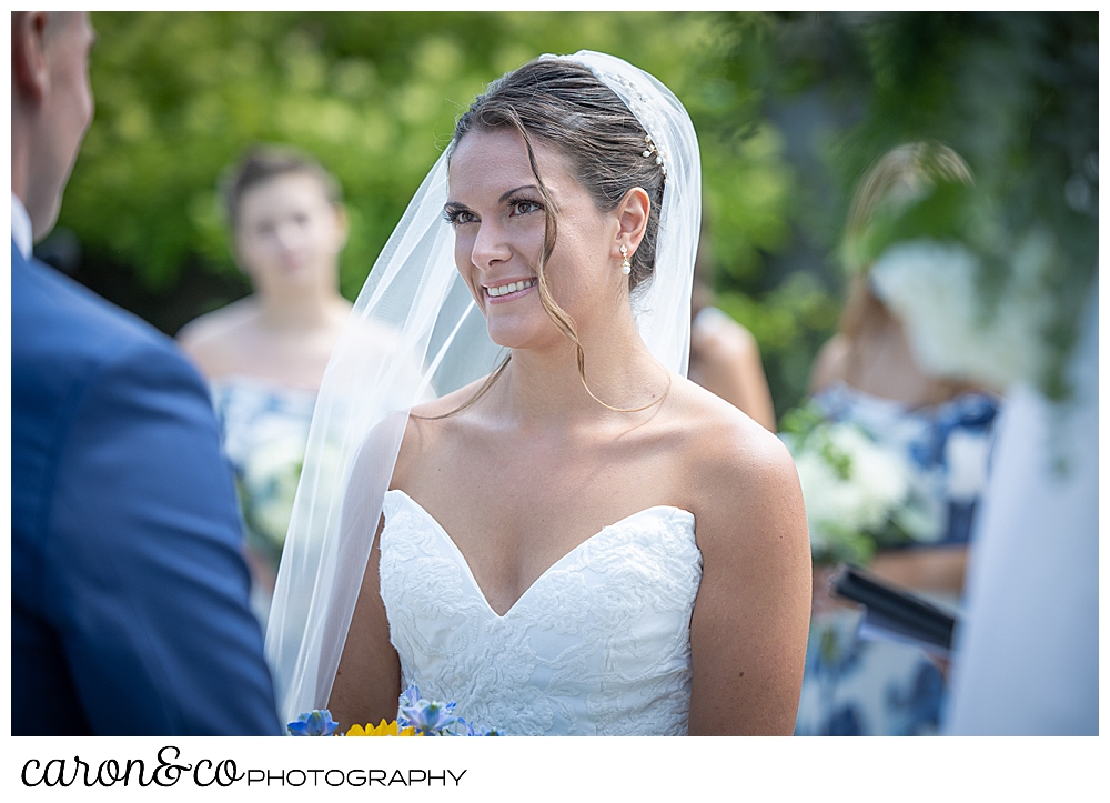 a dark haired, dark eyed bride, wearing a white strapless dress and veil, smiles at her groom during their outdoor ceremony at their Kennebunkport wedding at the Colony Hotel
