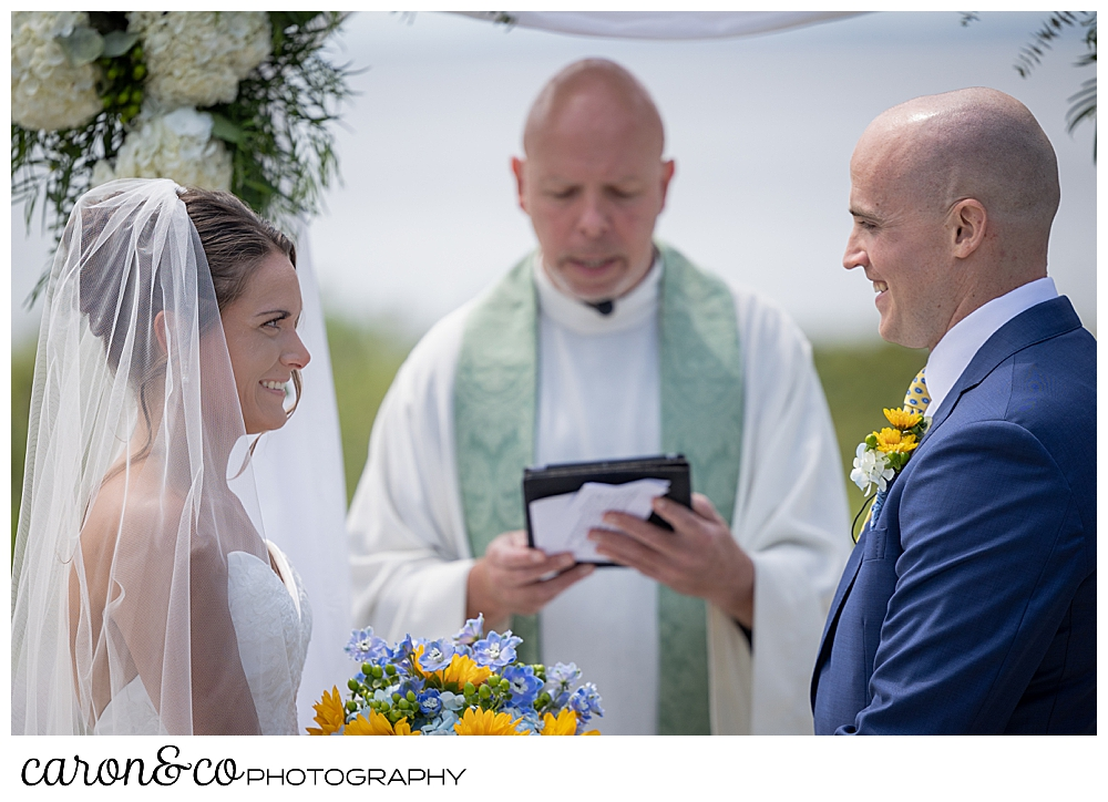 a priest reads while on either side stands a bride and groom, smiling at each other at a Kennebunkport wedding at the Colony Hotel