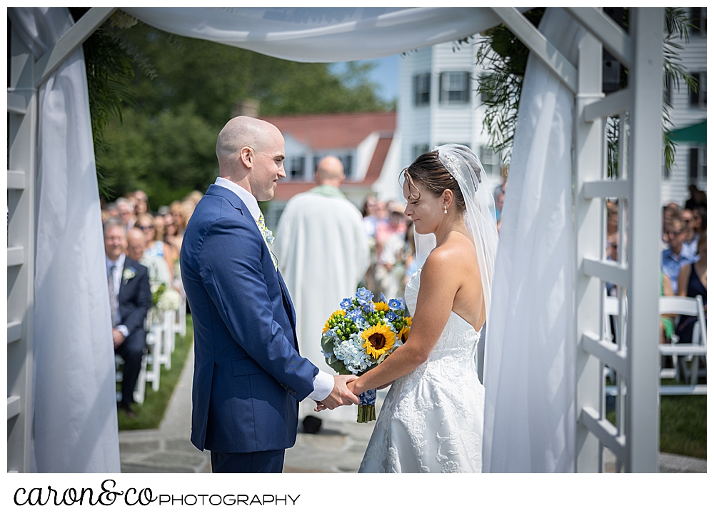 in the fore group are a bride wearing a white dress and veil, and a groom wearing a blue suit, holding hands; in the back ground is the officiant with his back to the camera