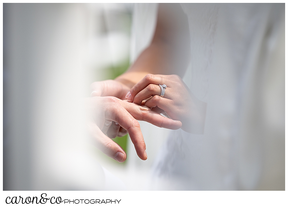 a bride's hand is holding the groom's hand, and she is putting a wedding band on his finger with her other hand