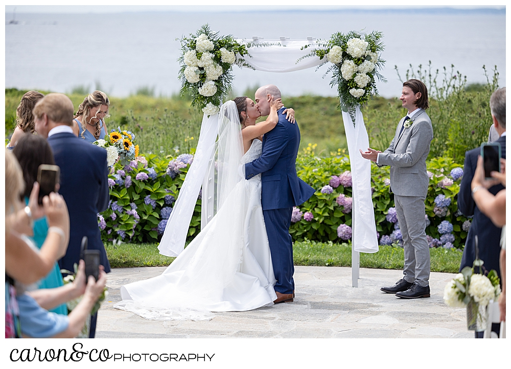 a bride and groom share their first kiss in front of an arbor at a Kennebunkport wedding at the Colony Hotel