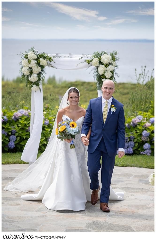 a bride wearing a white dress and veil, carrying a bouquet with blue hydrangeas and yellow sun flowers, is holding the arm of her groom who is wearing a blue suit, during the recessional at their Kennebunkport wedding at the Colony Hotel
