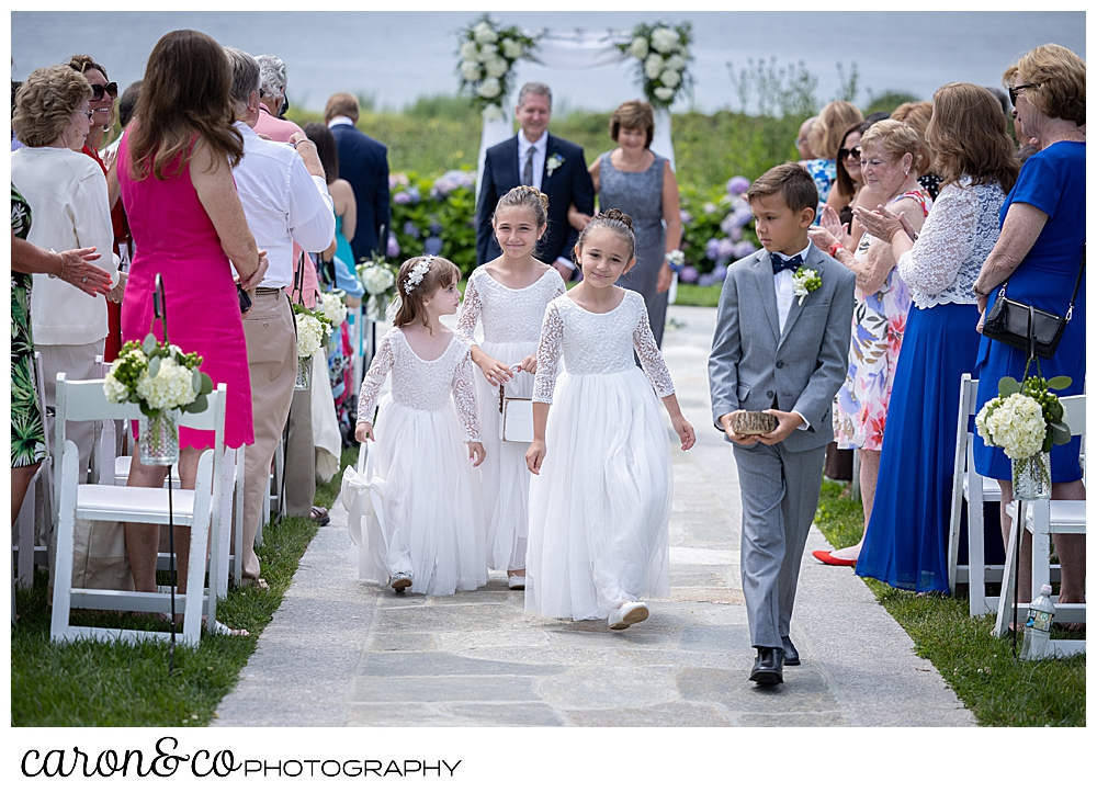 3 flower girls wearing white dresses, and a ring bearer wearing a gray suit are in the fore ground during a Kennebunkport wedding at the Colony Hotel, in the back ground are a women wearing a blue dress and a man wearing a blue suit