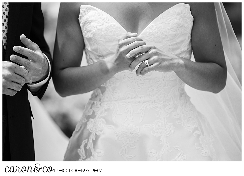 a black and white photo of a bride and groom, they are feeling the new wedding bands on their hands