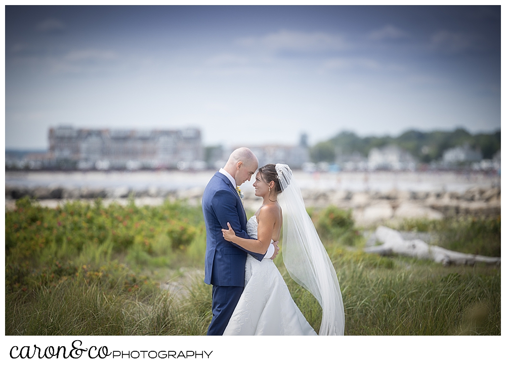a bride and groom stand facing each other, fore heads together, in the dunes at Colony Beach, at a Kennebunkport wedding at the Colony Hotel