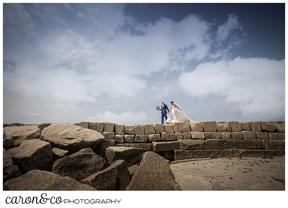 a bride and groom walk along the top of the Kennebunkport Breakwater, the groom is walking ahead of the bride and is holding her bouquet, the clouds and blue sky are in the background