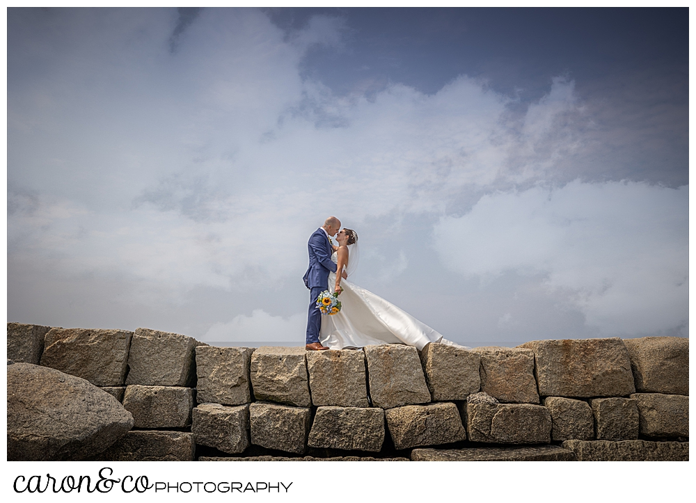 a bride and groom stand on the Kennebunkport Breakwater, they're facing one another and are about to kiss, Kennebunkport Maine