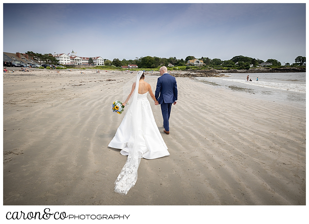 a bride and groom walk away from the camera on the Colony Beach, Kennebunkport, Maine