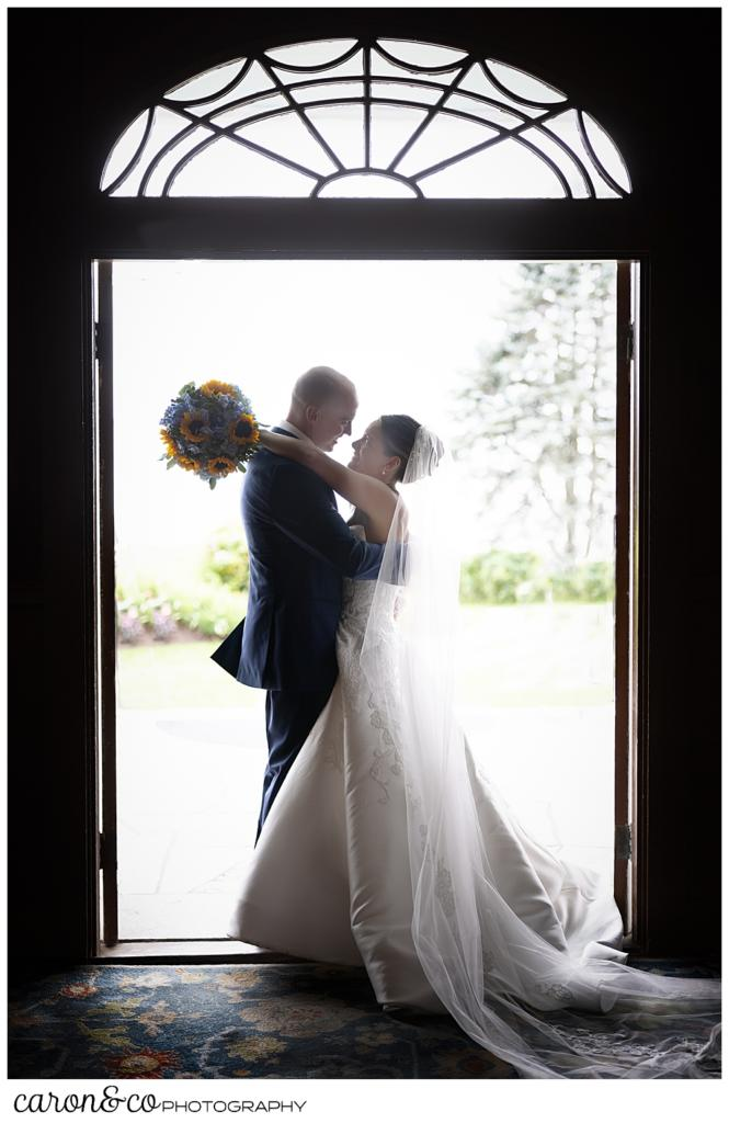 a bride and groom stand in the doorway of the Colony Hotel, their arms around each other, the bride has her bouquet of blue hydrangeas and yellow sun flowers behind the groom's neck