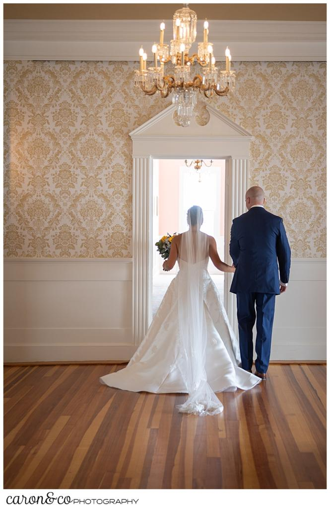 a bride and groom are walking through a banquet room at the Colony Hotel, during their Kennebunkport wedding at the Colony Hotel