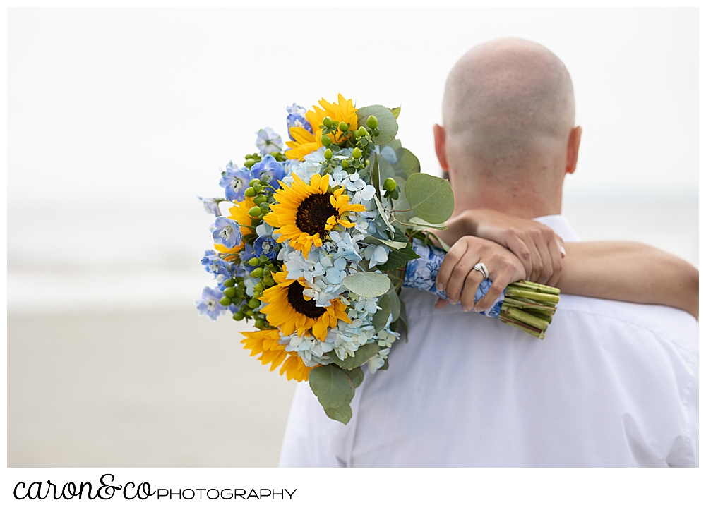 a groom is standing with his back to the camera, the bride's hands, holding a bouquet of blue hydrangeas and yellow sunflowers behind his back