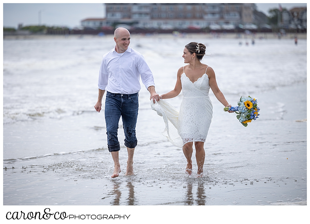 a bride and groom run in the water at Gooch's Beach, Kennebunk, Maine. The bride is wearing a short lace dress and holding a bouquet of blue hydrangeas and yellow sunflowers, the groom is wearing rolled up jeans, and a white shirt