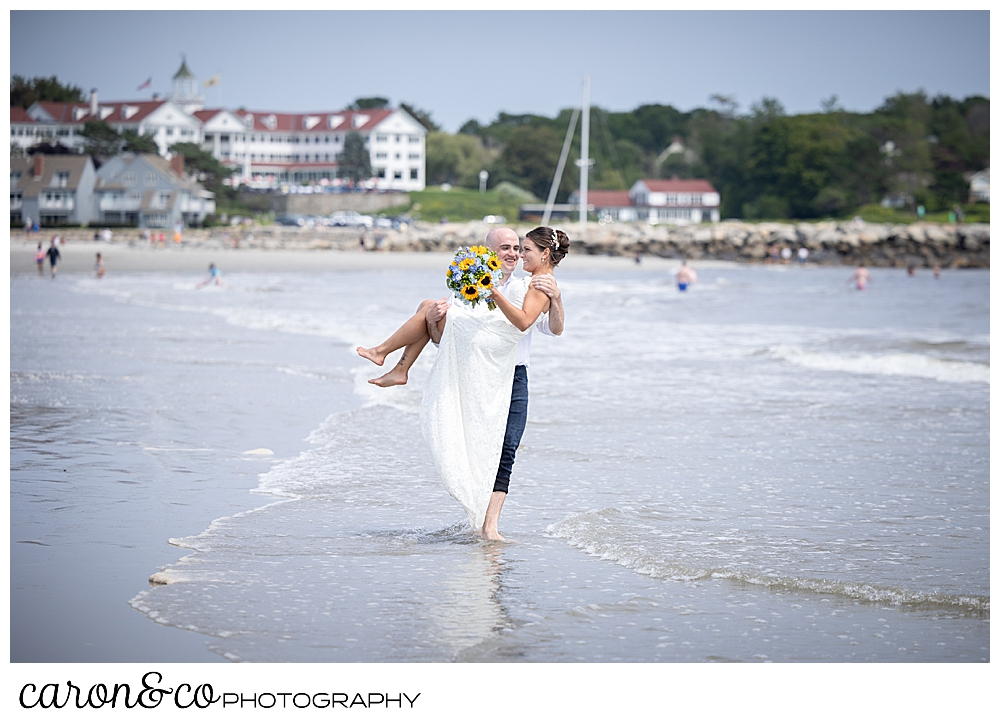 a groom has picked up a bride, and he's walking through the water at Gooch's Beach, the Colony Hotel is in the background