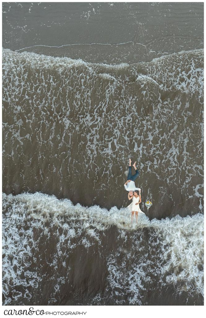 a view of a bride and groom lying down in the water, from a drone. The bride's legs are under the water, as waves come rolling in, Maine drone weddings