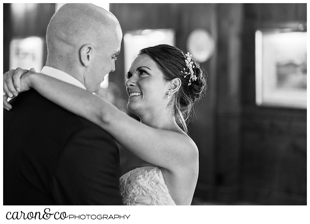 black and white photo of a bride smiling at her groom during their first dance at a Kennebunkport wedding at the Colony Hotel