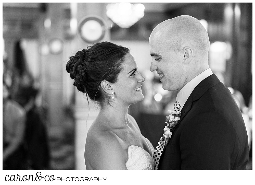 black and white photo of a bride and groom smiling at each other as they dance their first dance at a Kennebunkport wedding at the Colony Hotel