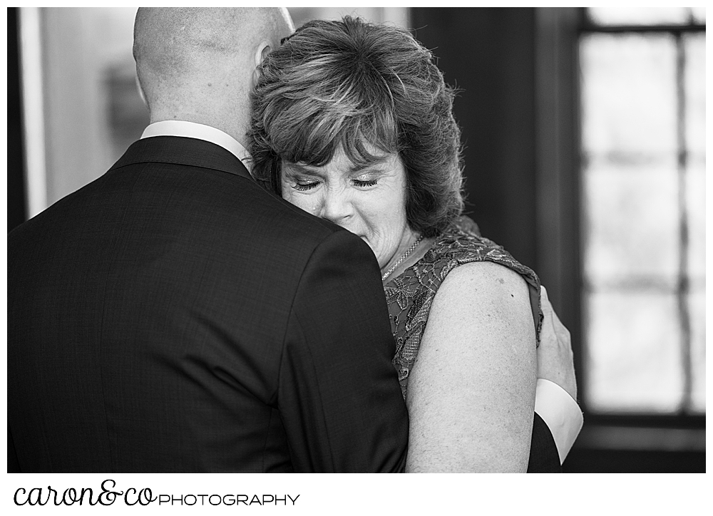 black and white photo of a mother son dance, the groom's back is to the camera, his mother's head is on his shoulder, her eyes are closed