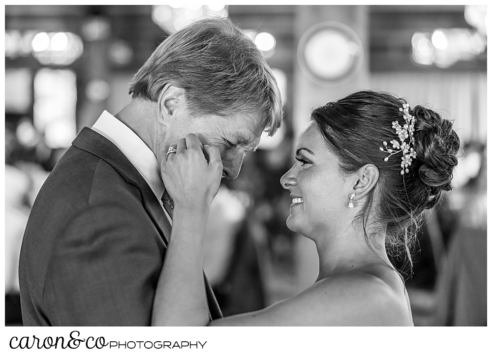 black and white photo of a bride and her father during the father daughter dance, the bride is brushing away a tear on her dad's cheek, at a Kennebunkport wedding at the Colony Hotel