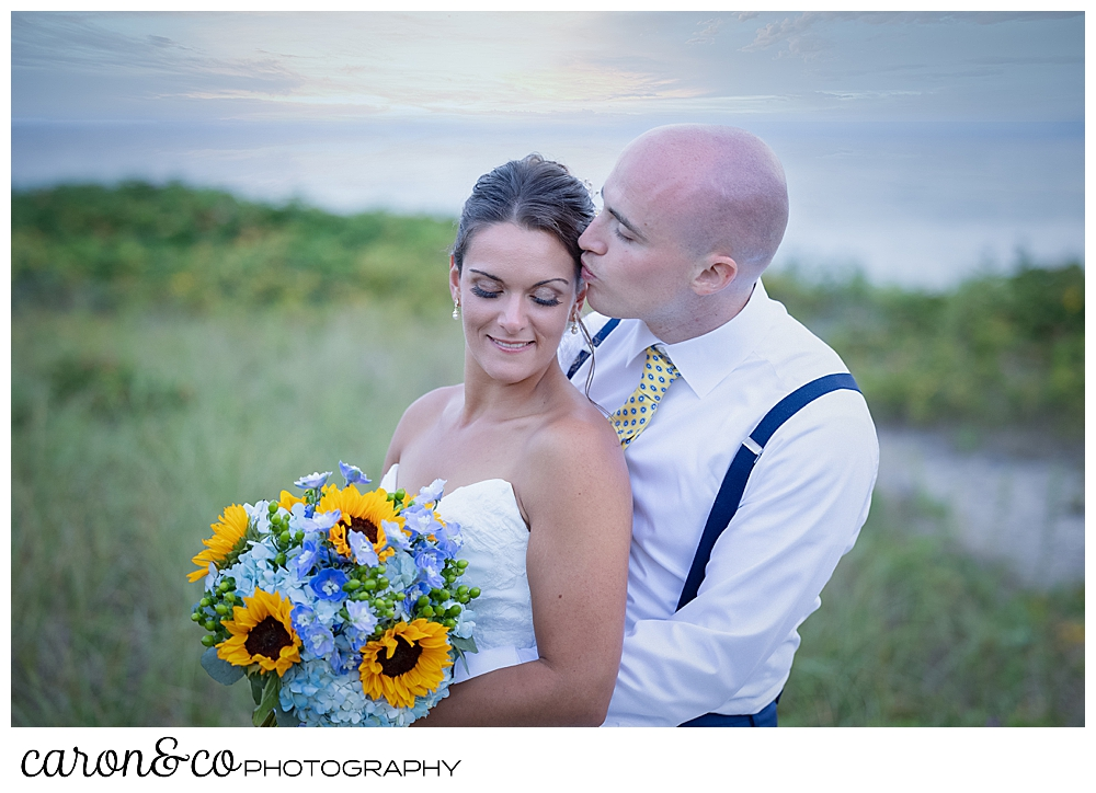 a groom stands behind his bride, kissing her temple, she holds a bouquet of blue hydrangeas and yellow sunflowers, they're in the dunes at Colony Beach, Kennebunkport, Maine