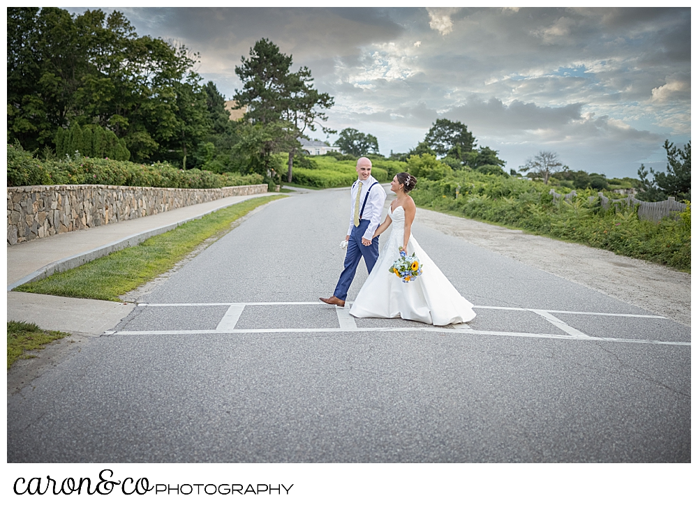 a bride and groom holding hands, cross the street in front of the Colony Hotel, at a Kennebunkport wedding at the Colony Hotel