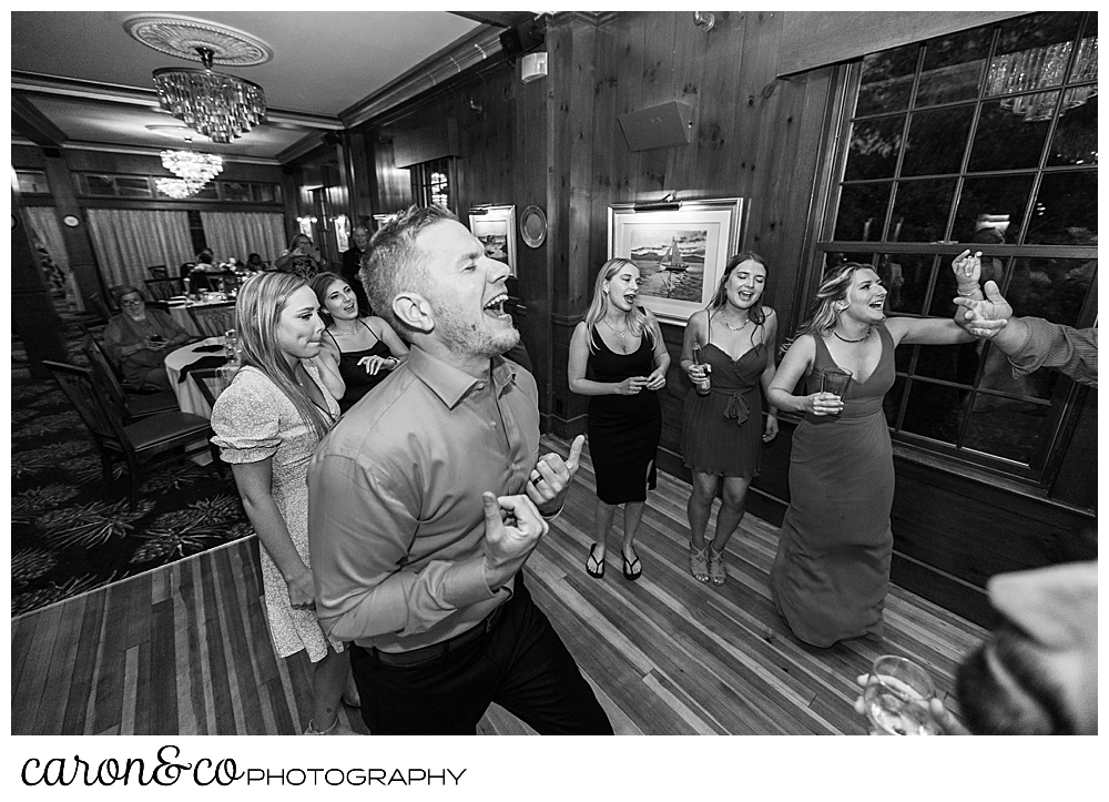 black and white photo of a ban dancing and singing, while guests dance around him