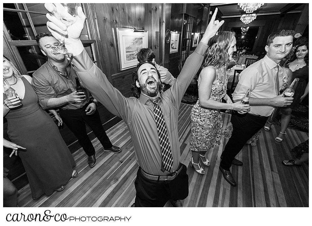 black and white photo of a man with his arms raised and his mouth open, while guests dance in the background