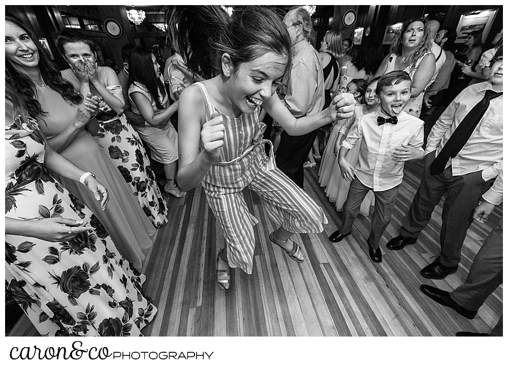 black and white photo of a woman in a striped jumpsuit, dancing while other guests dance around in the background