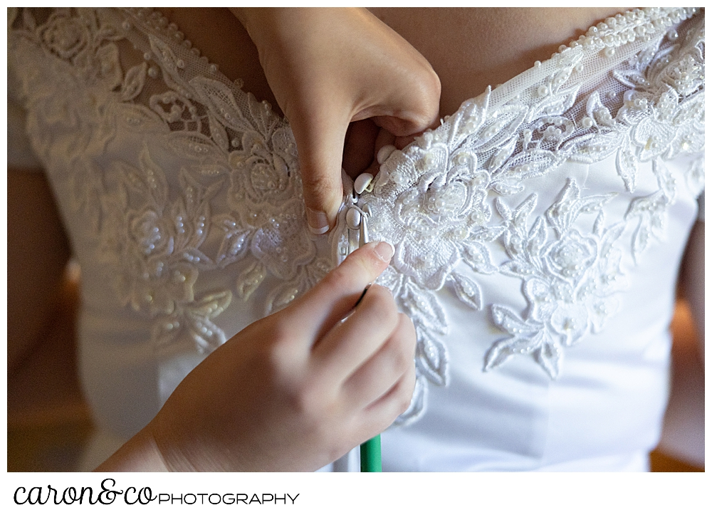 wedding dress being fastened in the back with a crochet hook