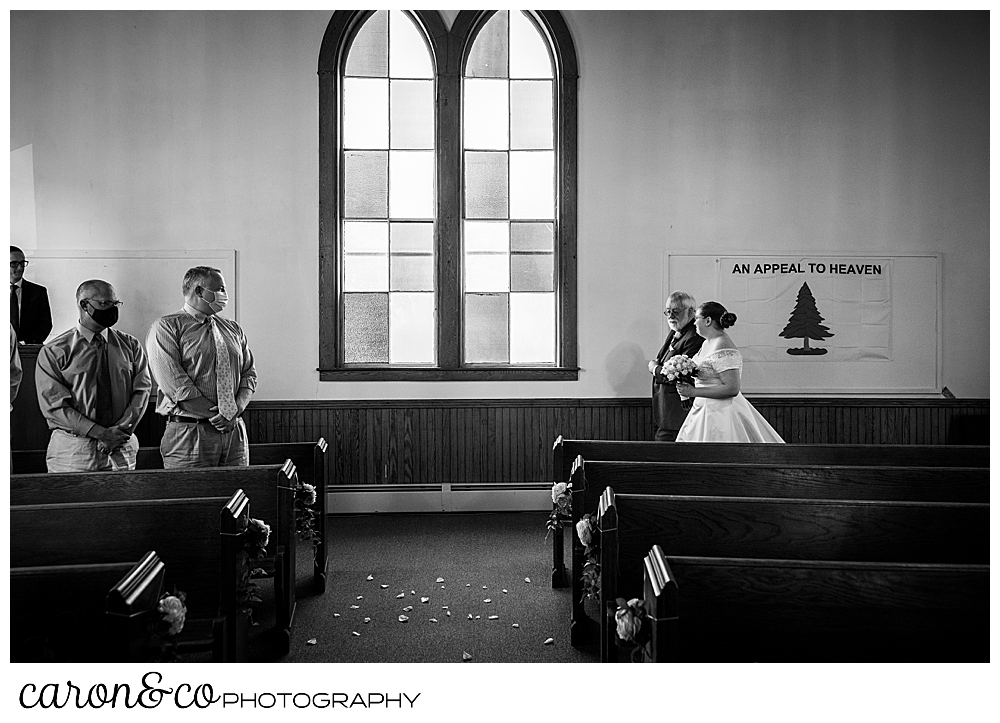 black and white photo of a bride and her father approaching the aisle in the Peru Maine Baptist Church