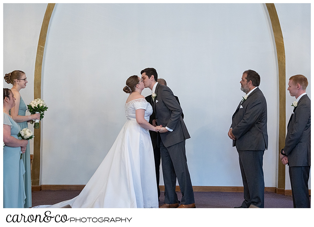 a bride and groom have their first kiss at the Peru Maine Baptist Church, during a sweet western Maine wedding