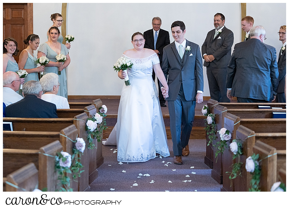 a bride and groom during their recessional at the Peru Maine Baptist Church, during a sweet western Maine wedding ceremony
