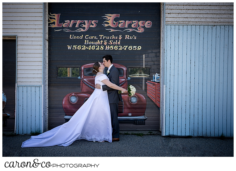 a bride and groom kiss in front of a car mural in Peru Maine, during a sweet western Maine wedding