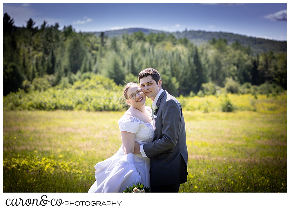 bride and groom portrait in a field in the mountains of western maine