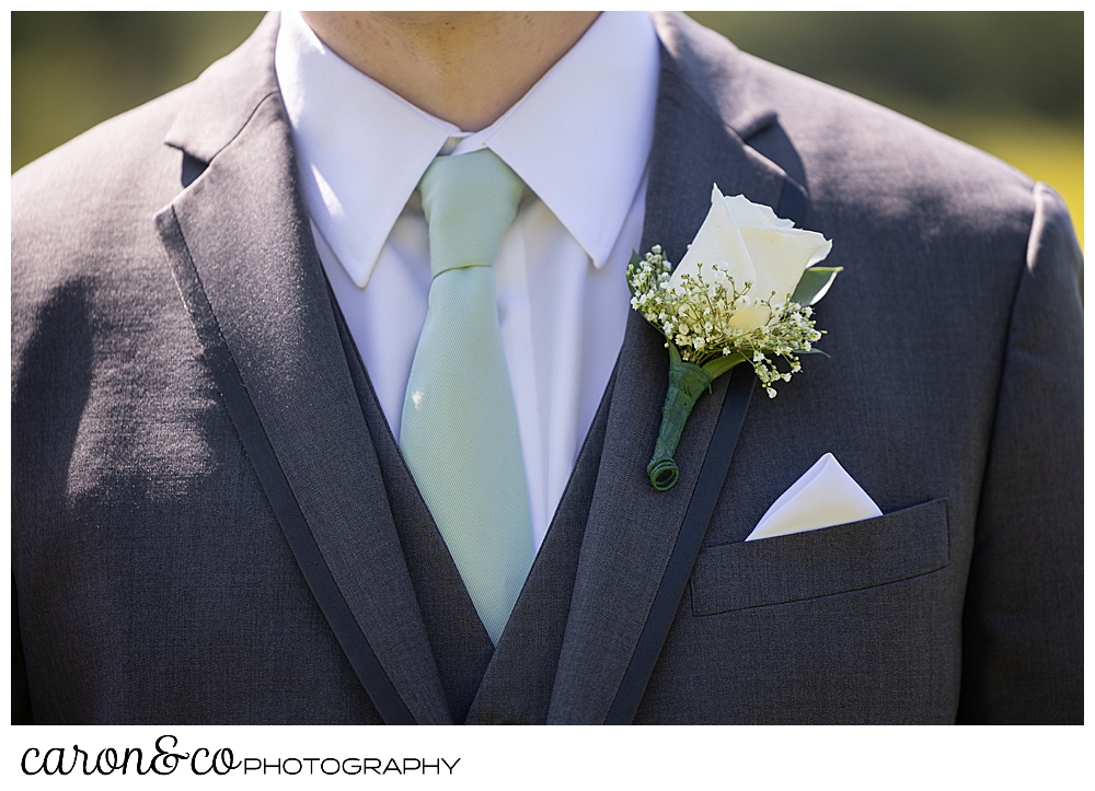 groom details of a green tie, a cream rose boutonniere, and a white pocket square,