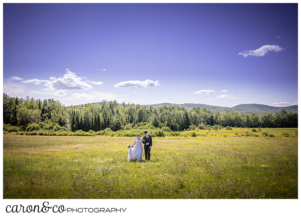 a bride and groom walking in a field, arms linked, during a sweet western Maine wedding