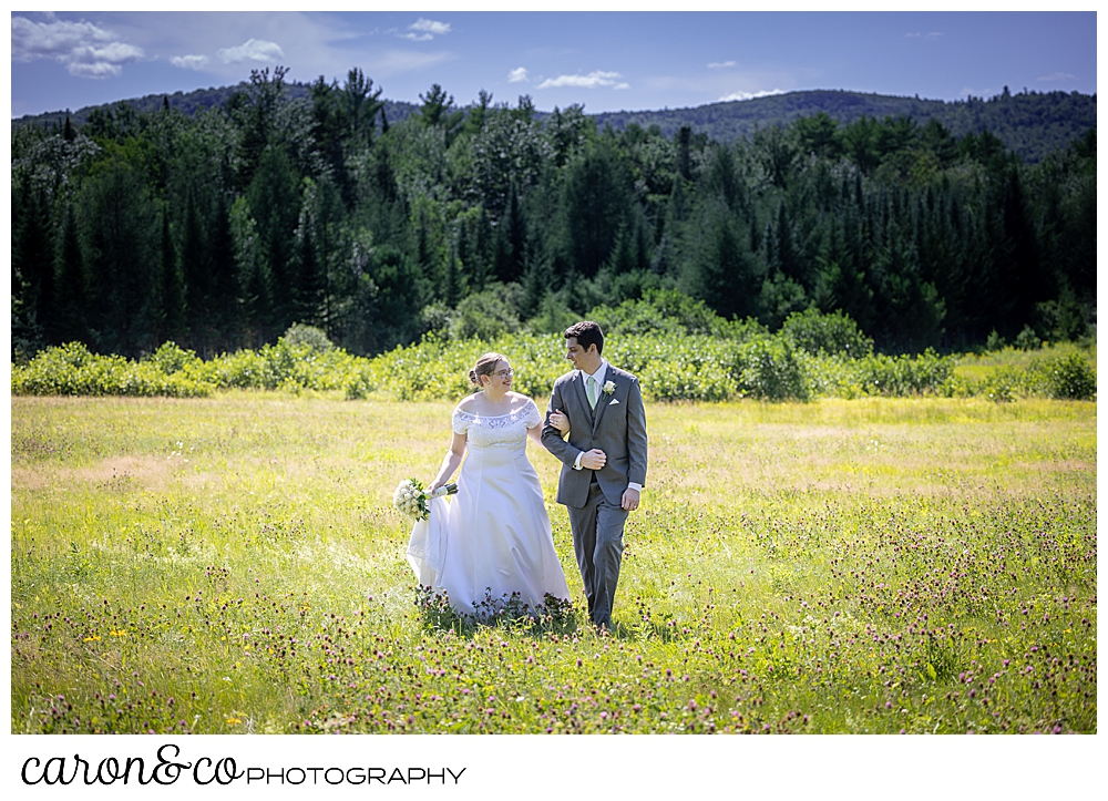 a bride and groom look at each other, while walking in a field, their arms linked
