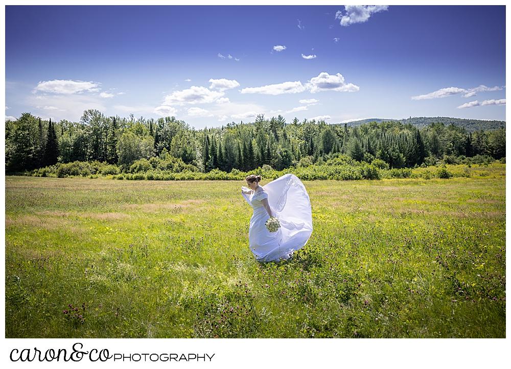 a bride twirls in a field in western Maine