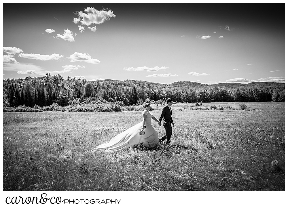black and white photo of a bride and groom holding hands, walking in a field, with mountains in the background, during a sweet western Maine wedding