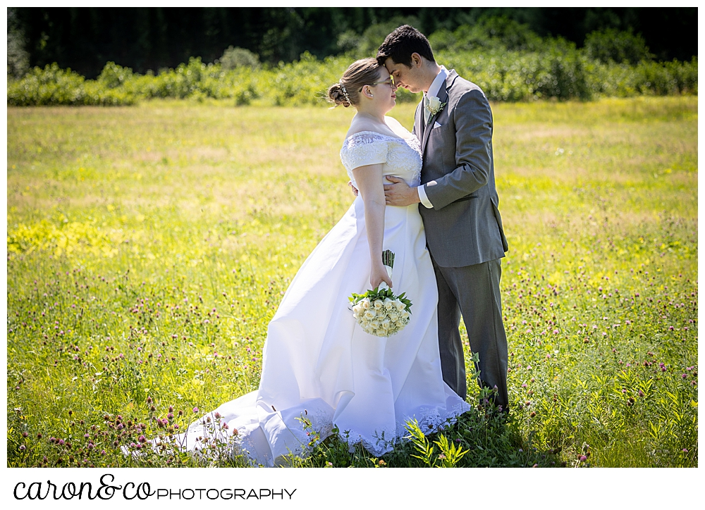 a bride and groom standing with their foreheads touching, in a field